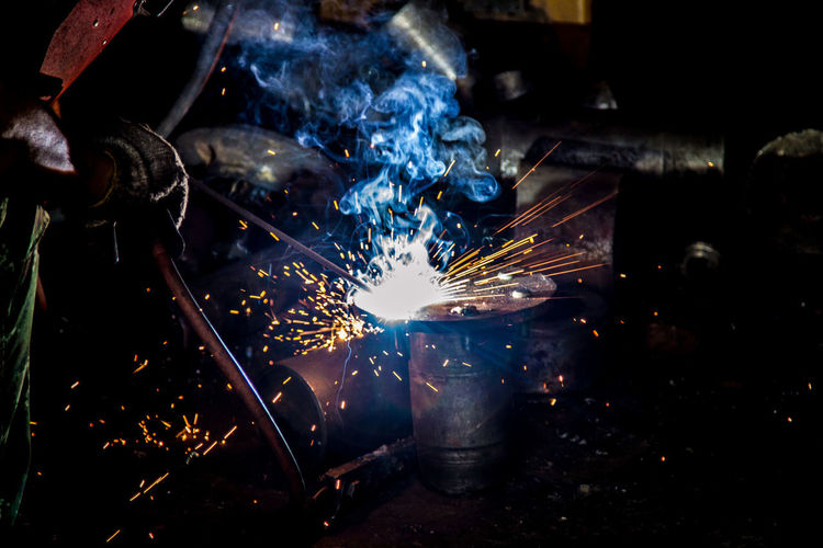 Blurred Motion Burning Factory Fire Fire - Natural Phenomenon Flame Glowing Hand Heat - Temperature Indoors  Industry Iron - Metal Melting Metal Metal Industry Motion One Person Real People Skill  Smoke - Physical Structure Sparks Welding Work Tool Working Workshop