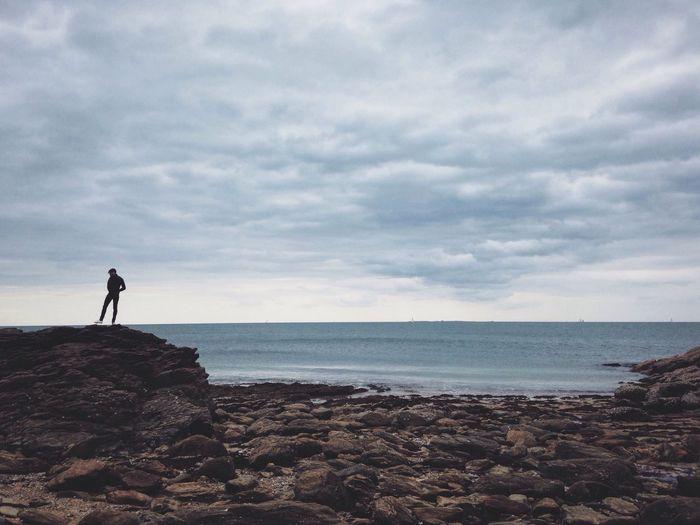 Man on rocky shore against sky