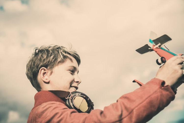 Low angle portrait of boy holding camera