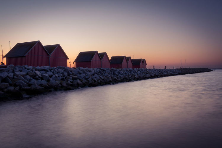 Beach Huts On Groyne In Sea Against Sky During Sunset