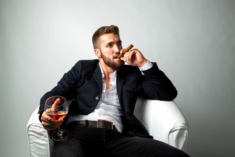 Attractive bearded man with a cigar, and a glass of whiskey in his hands is sitting in a white armchair Males  Drink Sitting Refreshment Alcohol One Person Glass Holding Men Drinking Glass Indoors  Young Men Males  Well-dressed Drinking Cigar Businessman Armchair Whiskey Bad Habit Beard Relaxing Break Success Isolated