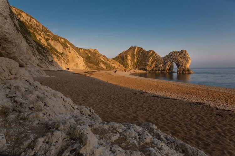 Durdle Door Dorset Jurassic Coast Britain Beach Sea Pebbles sunset Golden Hour Stone arch Cliffs