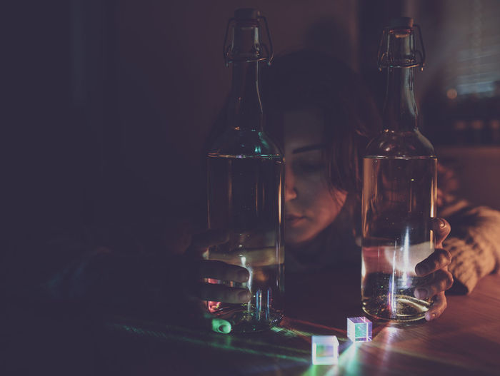 Thoughtful woman with wine bottles on table in darkroom