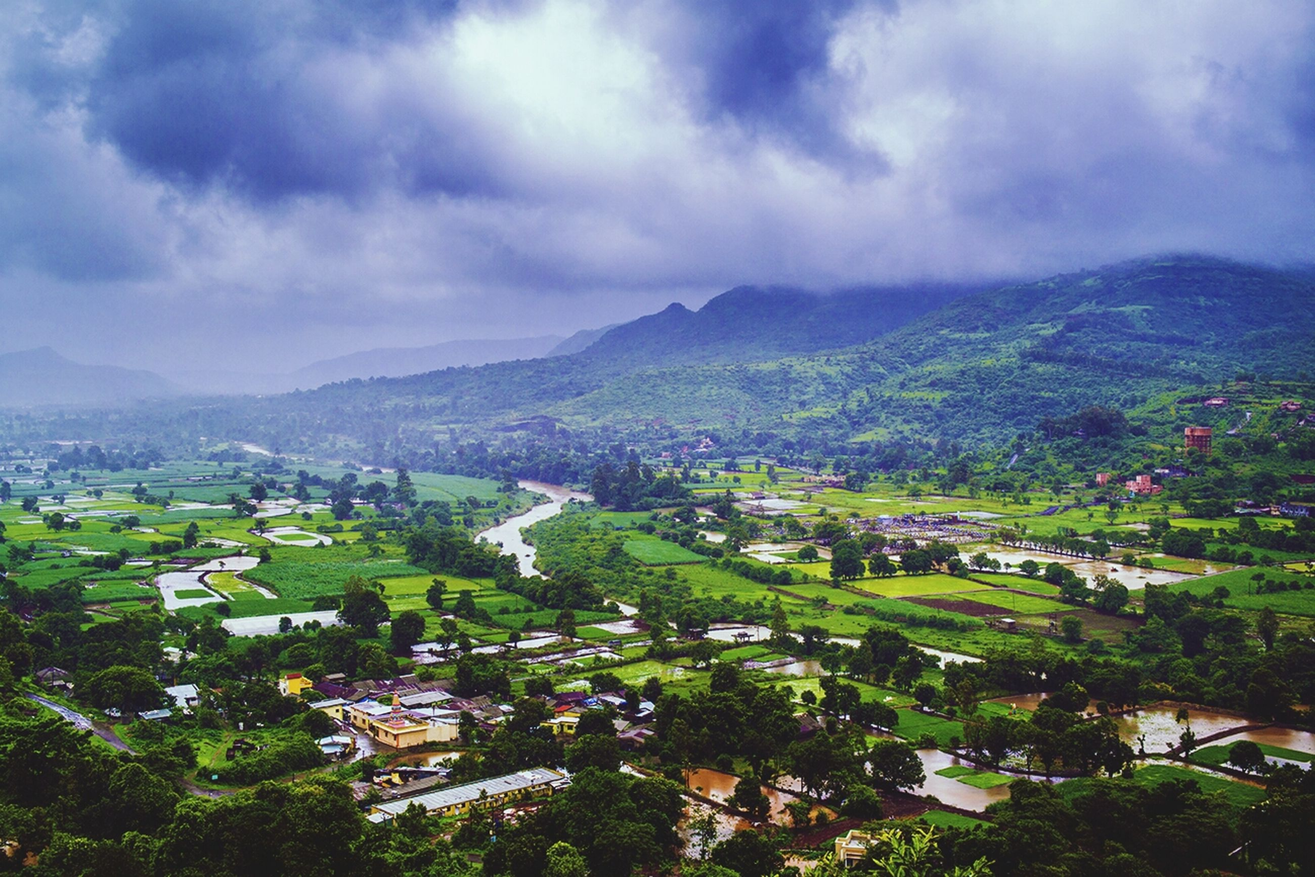 mountain, building exterior, sky, tree, architecture, built structure, cloud - sky, high angle view, mountain range, residential district, town, cityscape, house, crowded, residential structure, city, residential building, townscape, cloudy, cloud