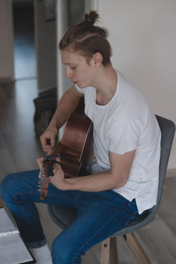 Side view of young man playing guitar at home