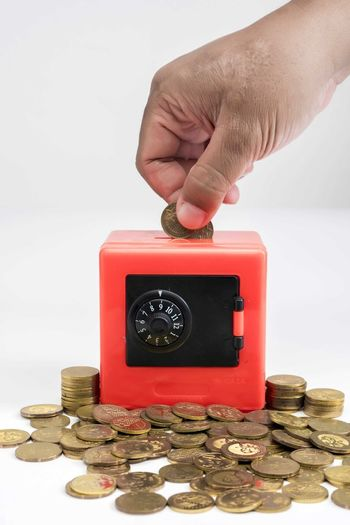 Hand holding coins and put into red safe box Human Hand Hand Human Body Part Coin Indoors  Real People Red Finger Human Finger Unrecognizable Person Finance Holding One Person Studio Shot Close-up Technology Body Part Savings Stack