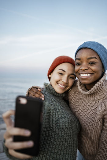 Portrait of a smiling young woman using mobile phone in winter