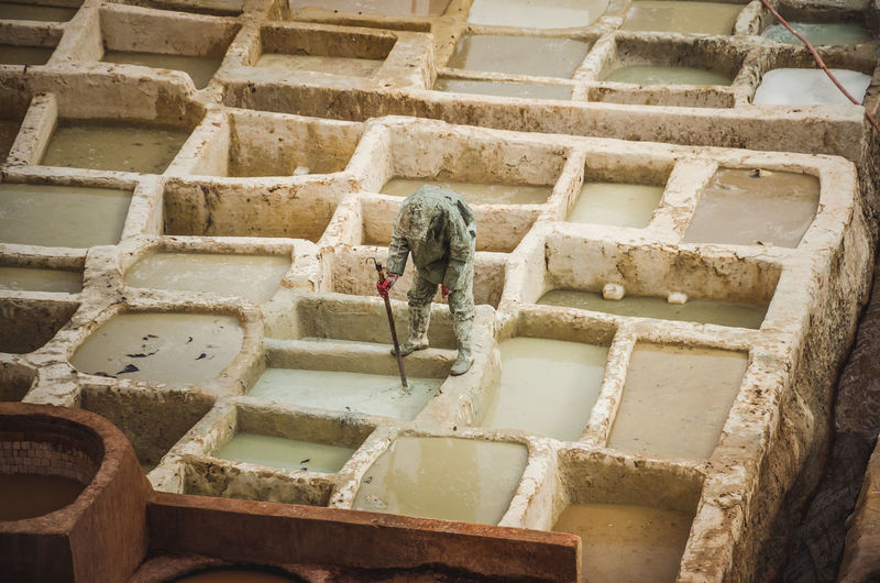 Low angle view of man working on wall