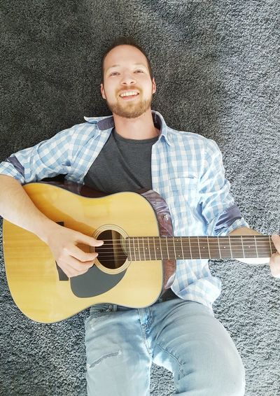 Man lying on carpet playing acoustic guitar Songwriter Acoustic Guitar Smiling Carpet Lying Down Lying On The Floor Playing Guitar Guitarist Musician Making Music Guitarist Fun Plucking An Instrument Musical Instrument Human Hand Men Performance Rock Music Classical Guitar Analogue Sound