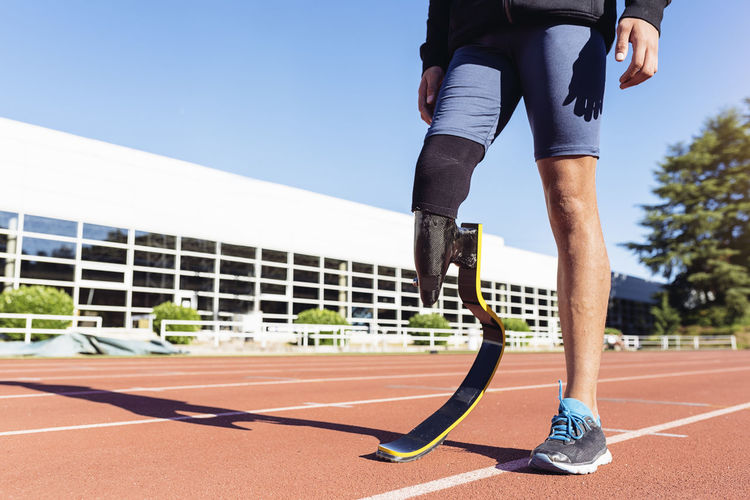 Low section of athlete with prosthetic leg standing on running track