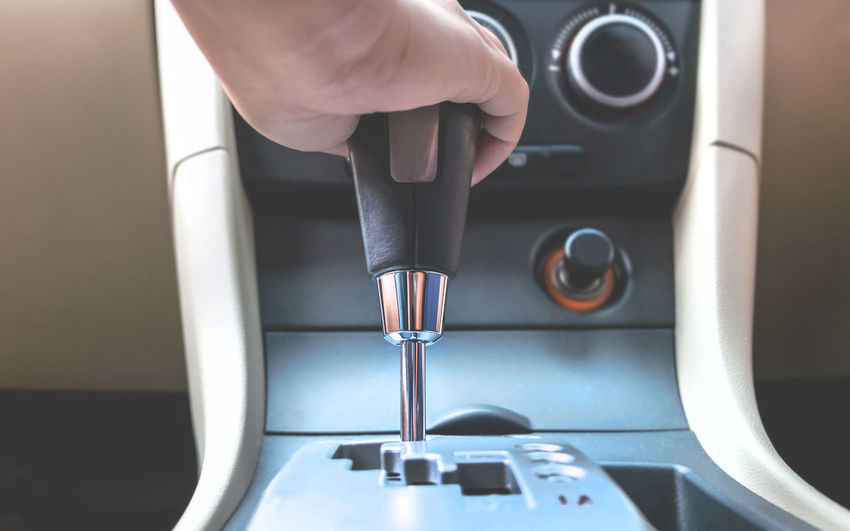 Cropped hand holding gear shift in car