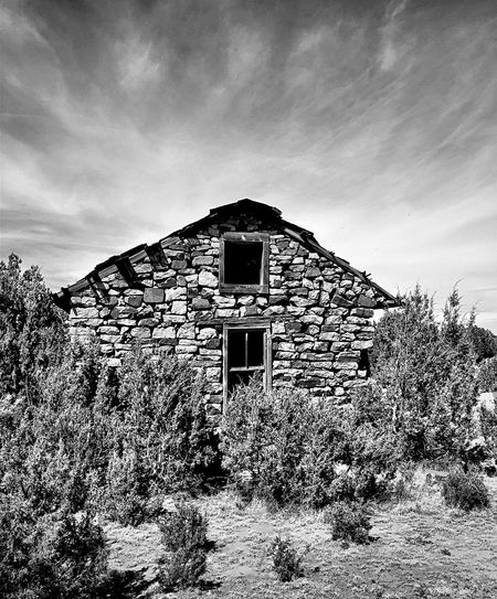 """""""One With Nature"""" An abandoned ranch house, hand built with surrounding natural stones, sits re-assimilating in with the natural environment off State Highway 3 in rural New Mexico, USA. Stone Stonehouse Natural Beauty Newmexicophotography Old House Blackandwhite Photography Abandoned Buildings NewMexicoTRUE"""