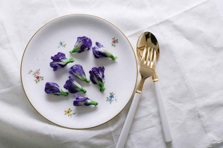 Butterfly pea the edible flower. Breakfast Butterfly Pea Directly Above Edible Flowers Flower Flowers Food Fork Freshness Healthy Eating Healthy Food Herbal Overhead View Plate Ready-to-eat Served Serving Size Spoon Still Life Tablecloth Visual Feast
