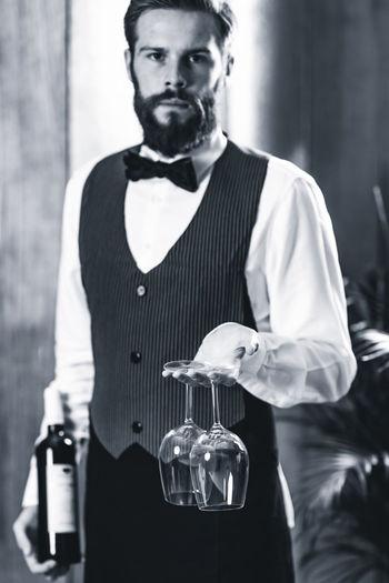 Portrait of bartendar holding wineglasses and bottle in bar