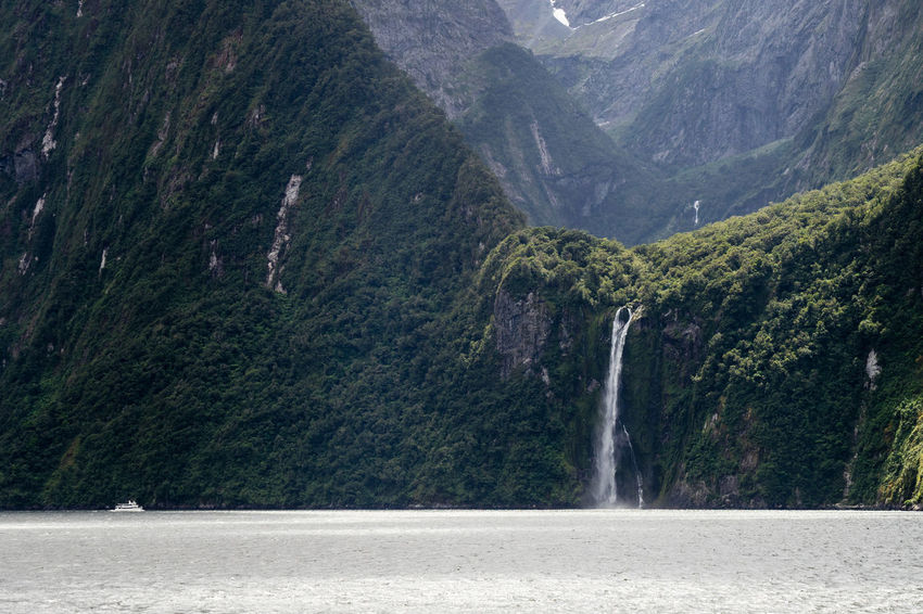 A sightseeing ship is dwarfed by a tall waterfall in a fjord in southern New Zealand. Beauty In Nature Boat Day Majestic Mountain Mountain Range Nature Non-urban Scene Outdoors Scenics Ship Ships Tranquil Scene Tranquility Water Waterfall Waterfront