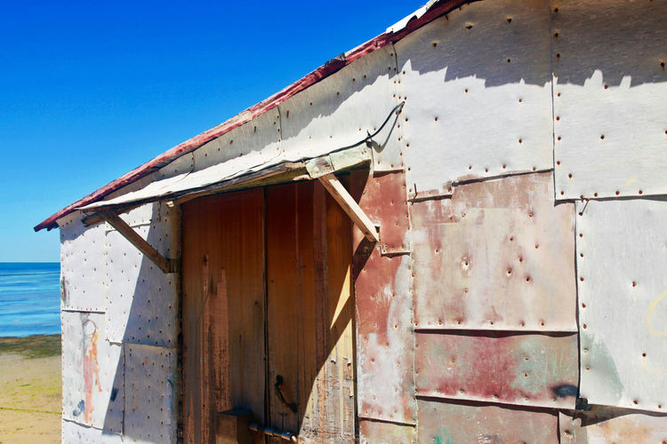 Abandoned house against clear blue sky at beach during sunny day