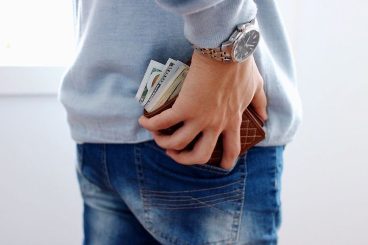 Midsection of person putting wallet in back pocket while standing at home