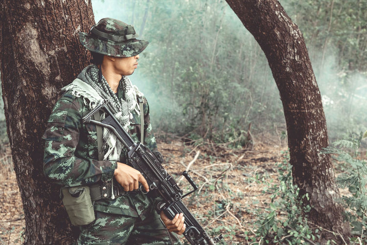 Male army soldier holding gun while standing in forest