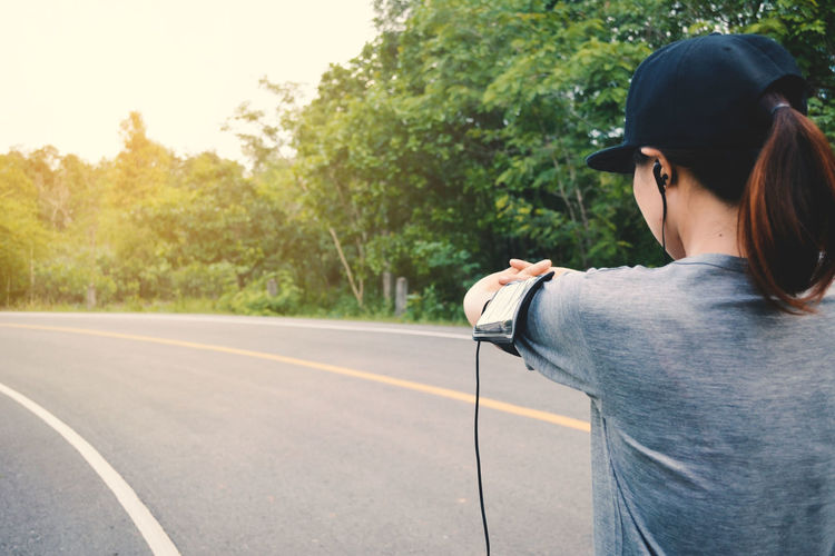 Rear view of woman listening to music while stretching on road