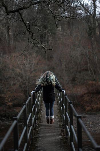 Rear view of woman jumping on footbridge in forest