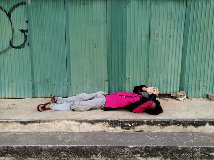 Full Length Of Man Lying On Footpath
