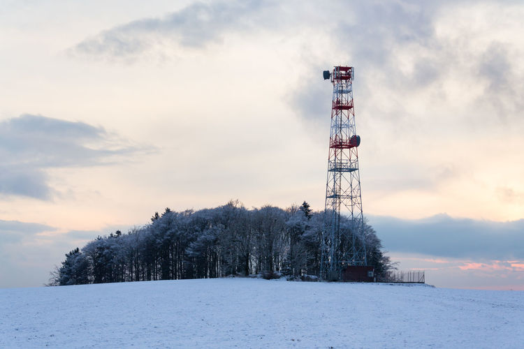 Communications tower on snow covered land against sky