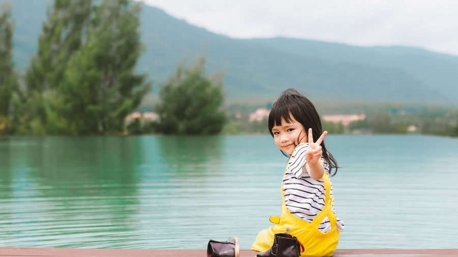 Beauty In Nature Casual Clothing Day Focus On Foreground Hairstyle Lake Leisure Activity Lifestyles Looking At Camera Mountain Nature One Person Outdoors Portrait Real People Scenics - Nature Smiling Water Young Adult Young Women
