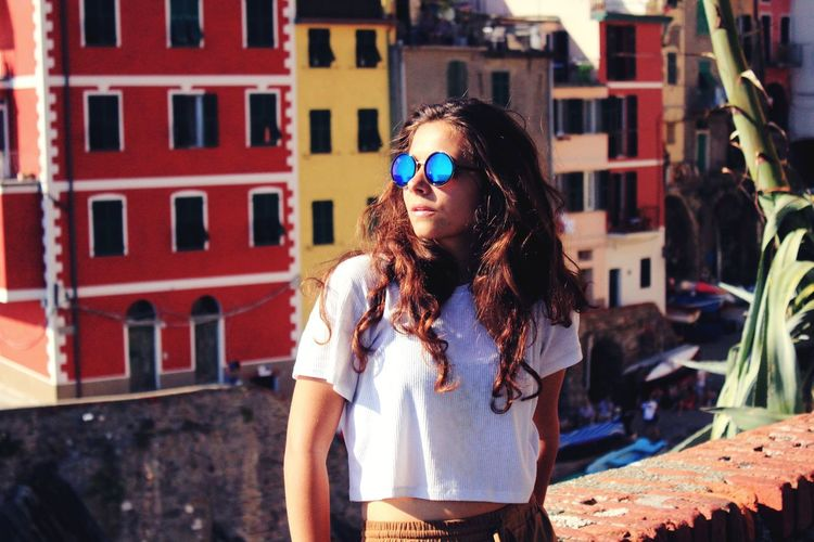 Young Woman Wearing Sunglasses Standing In City