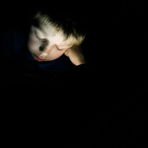 Child's face illuminated by the light of a digital device. Black Background Real People One Person Lifestyles Boys Childhood Leisure Activity Close-up Night technology digital insomnia