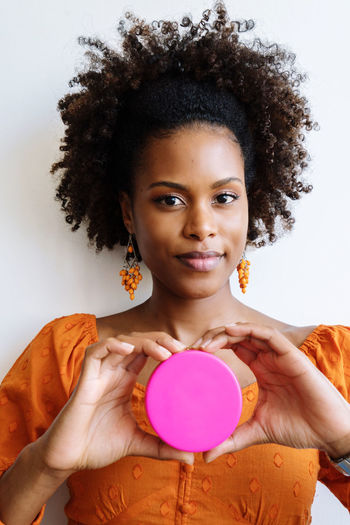 Portrait of a beautiful black woman with afro holding round pink beauty product