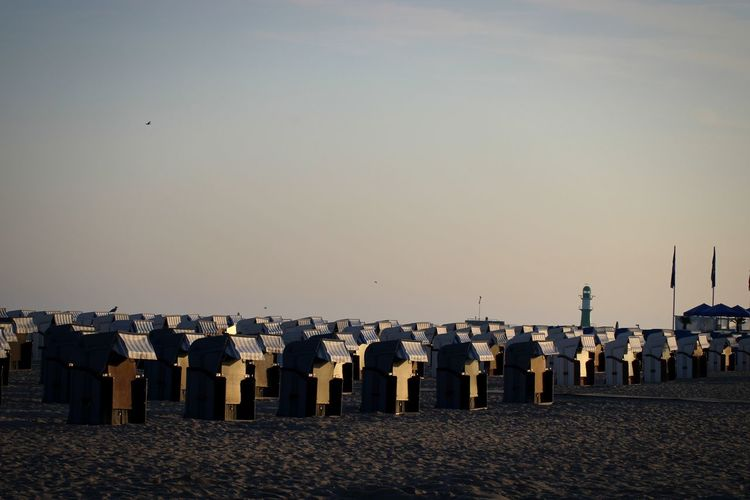 Row of hooded beach chairs against clear sky