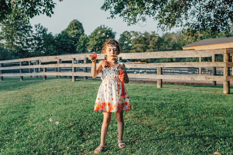 Full length of girl blowing bubbles while standing on field