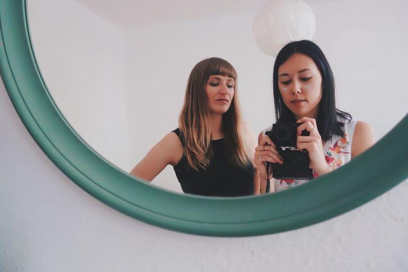 Beautiful Young Women Taking Photo In Mirror