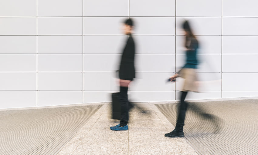 Blurred Motion Of Man And Woman Walking On Footpath
