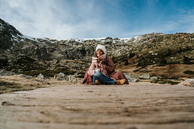 Woman wearing knit hat sitting on footpath with dog against mountains