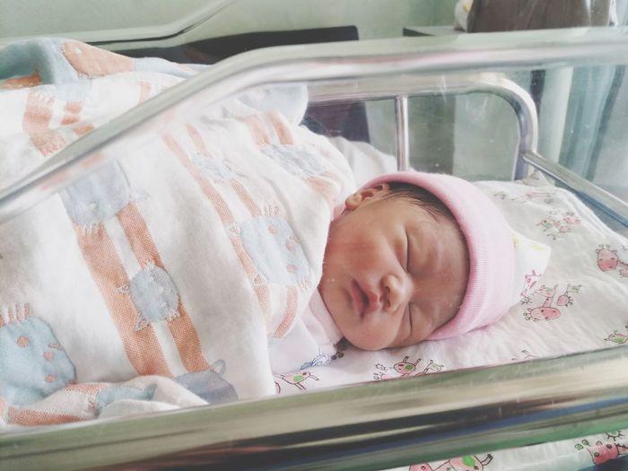 High angle view of cute baby girl sleeping on crib in hospital