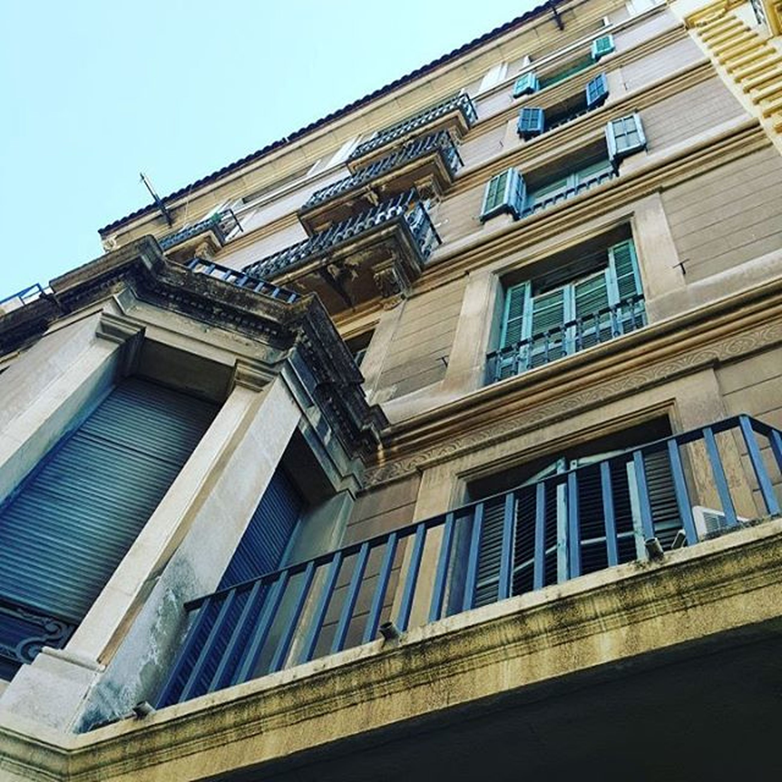 architecture, building exterior, built structure, low angle view, window, building, residential building, facade, residential structure, city, clear sky, sky, balcony, outdoors, day, no people, blue, exterior, sunlight, house