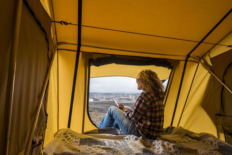 Side view of woman using phone while sitting in tent