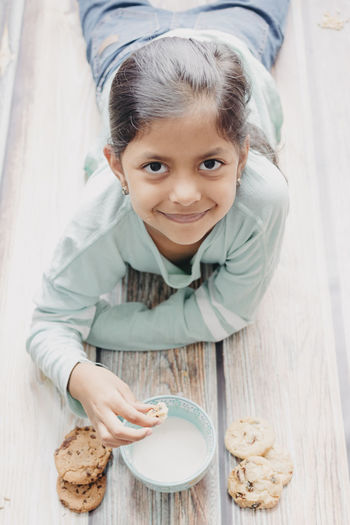 High angle portrait of cute smiling girl eating cookie while lying on hardwood floor
