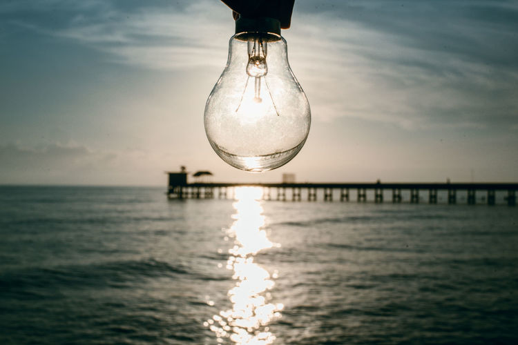 Reflection of illuminated light bulb on sea against sky
