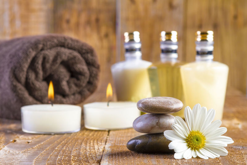 Aromatherapy Aromatherapy Oil Beauty Body Care Burning Candle Close-up Domestic Room Fire Flower Group Of Objects Health Spa Indoors  Luxury Nature No People Pebble Relaxation Softness Spa Treatment Still Life Therapy Towel Wellbeing Wood - Material