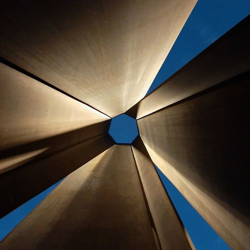 Low angle view of illuminated ceiling against sky