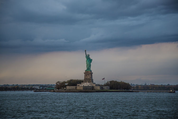 Statue Of Liberty Thunderclouds Architecture Built Structure City Cloud - Sky Day Female Likeness Human Representation Monument Nature No People Outdoors Sculpture Sea Sky Statue Storm Cloud Thunder Thunderstorm Travel Travel Destinations Water Waterfront
