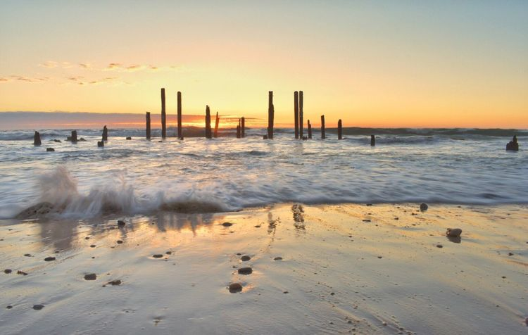 EyeEm Selects Sunset Sea Water Beach Nature Beauty In Nature Scenics Horizon Over Water Sky Tranquil Scene Sand Tranquility Wooden Post Outdoors No People Wave Day