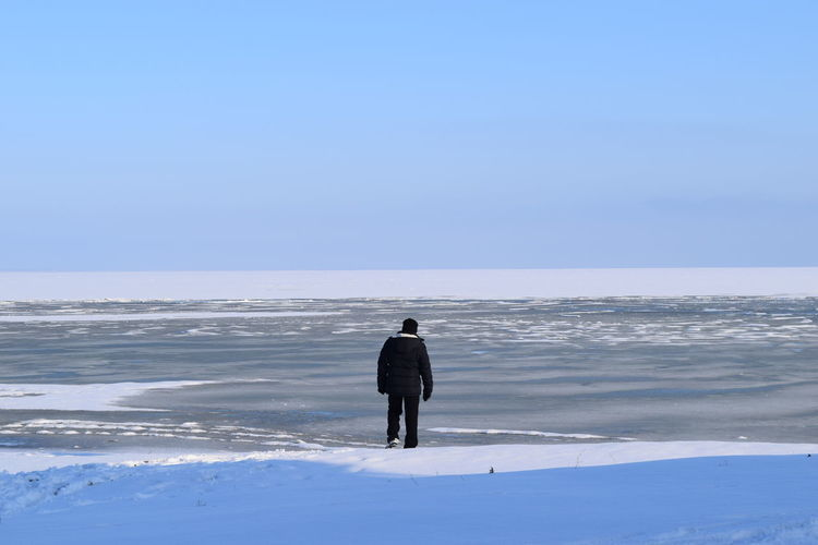 Rear View Of Man Walking On Frozen Lake Against Sky