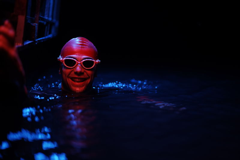 Portrait of smiling man in swimming pool at night