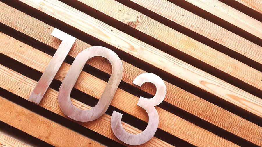 Close-up of number on wooden wall