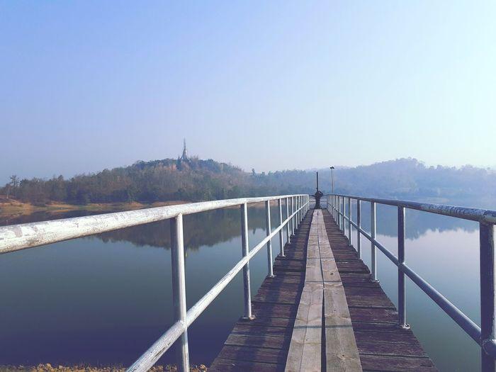 Bridge over calm lake against clear sky