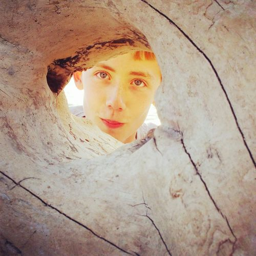 Portrait of teenager boy looking through hole in rock