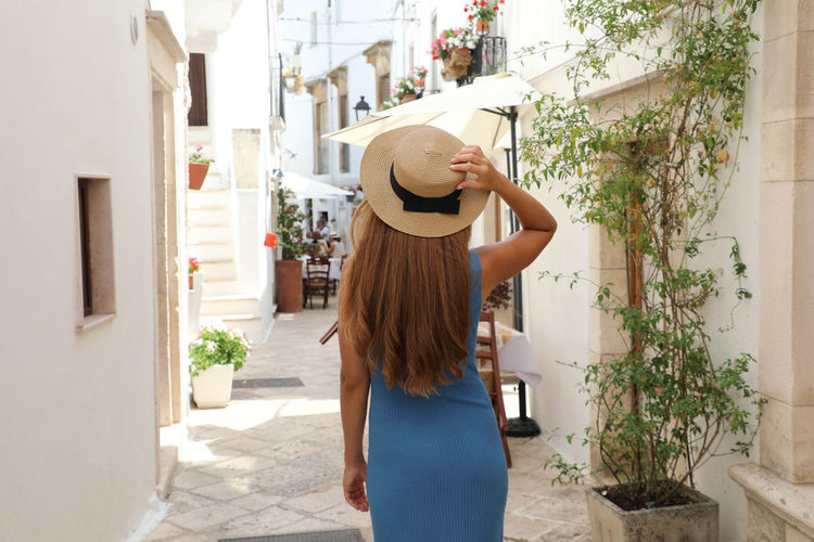Woman wearing hat standing against wall